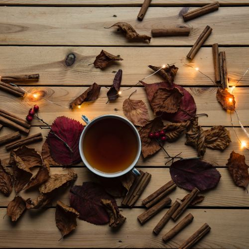 A cup of brown tea surrounded by cinnamon sticks and a few lights.