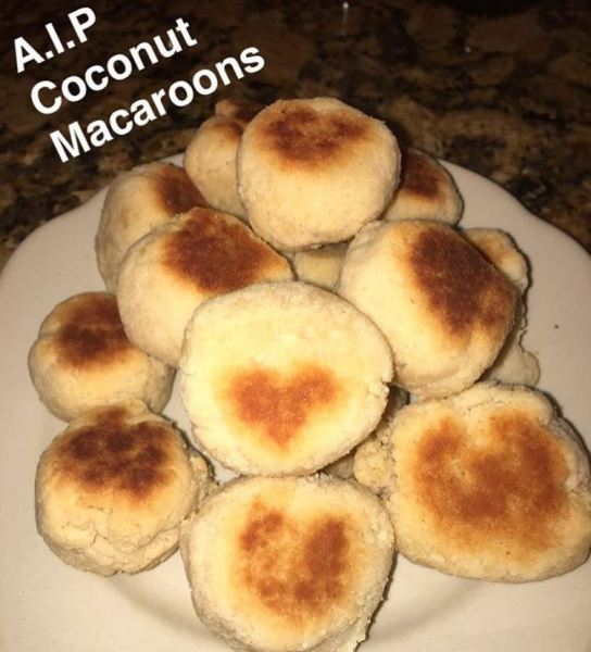 yellow coconut macaroons sitting on a white plate.