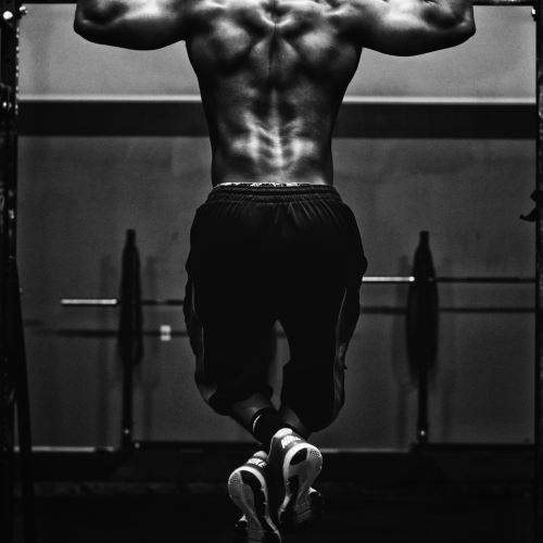 BLACK AND WHITE PHOTO OF MUSCULAR MAN DOING PULL UP FROM BEHIND