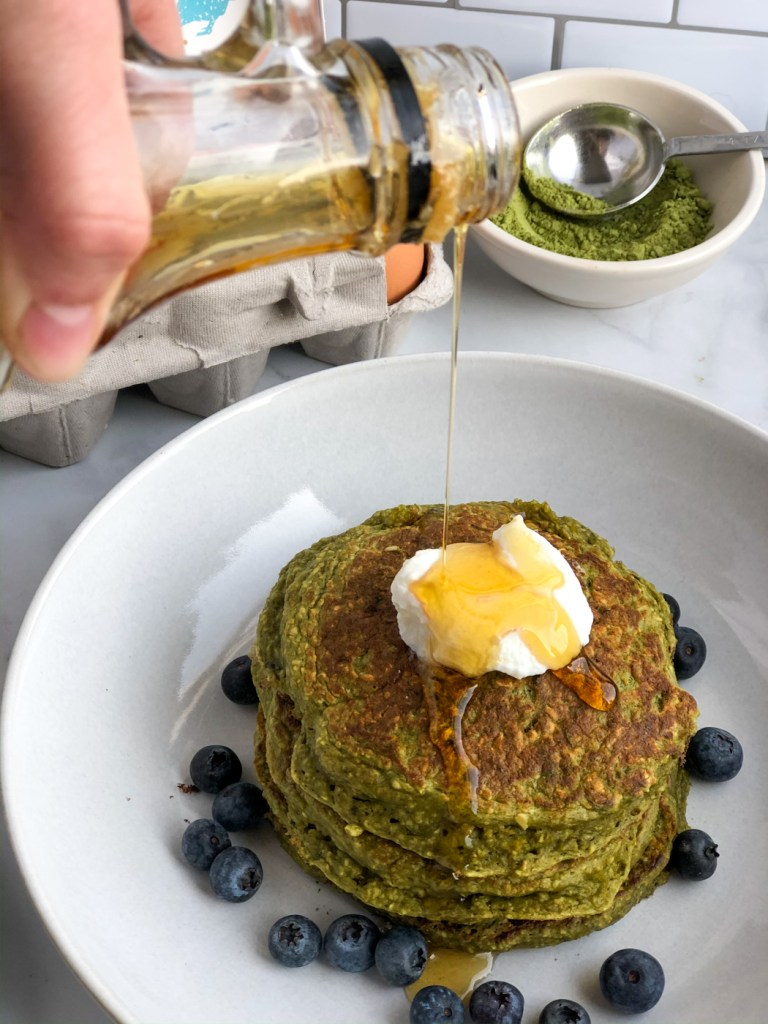 pouring syrup over stack of healthy matcha pancakes