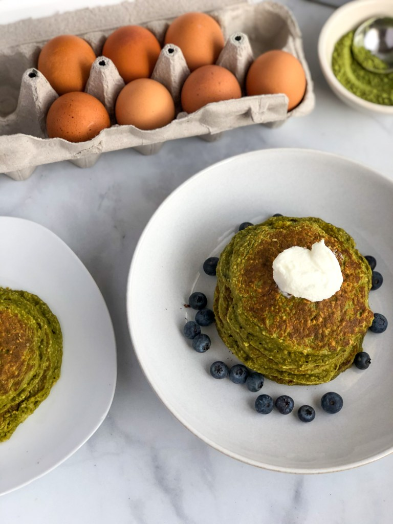 Stack of healthy matcha pancakes with blueberries and greek yogurt on top