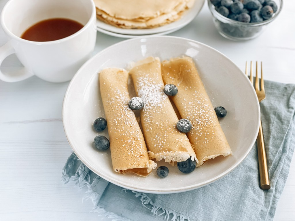 Plate of Scandinavian pancakes with powdered sugar and blueberries