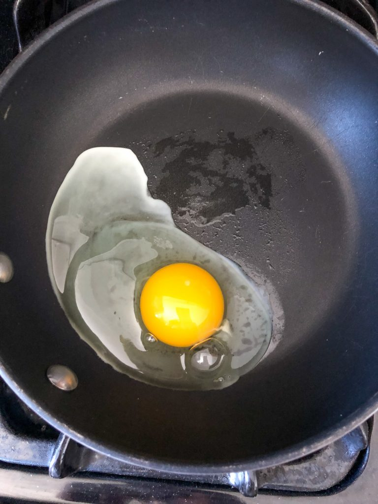 Cracked egg in saucepan