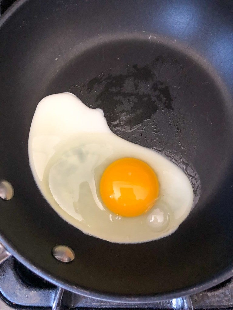 Egg in pan with whites starting to set
