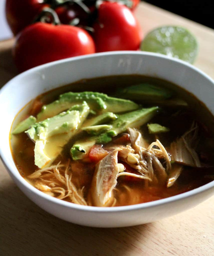 Bowl of healthy chicken and fresh tomato tortilla soup