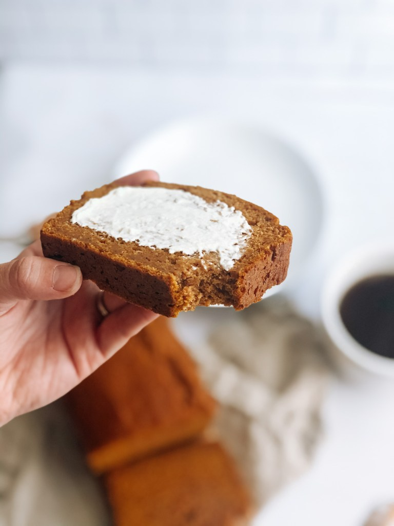 holding a slice of healthy pumpkin bread with cream cheese on top