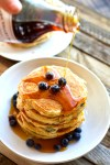 Pouring maple syrup over Stack of super fluffy greek yogurt and blueberry pancakes