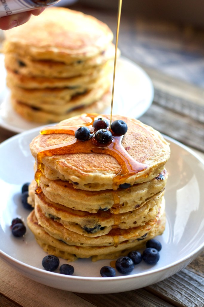 Pouring maple syrup over a stack of super fluffy greek yogurt and blueberry pancakes