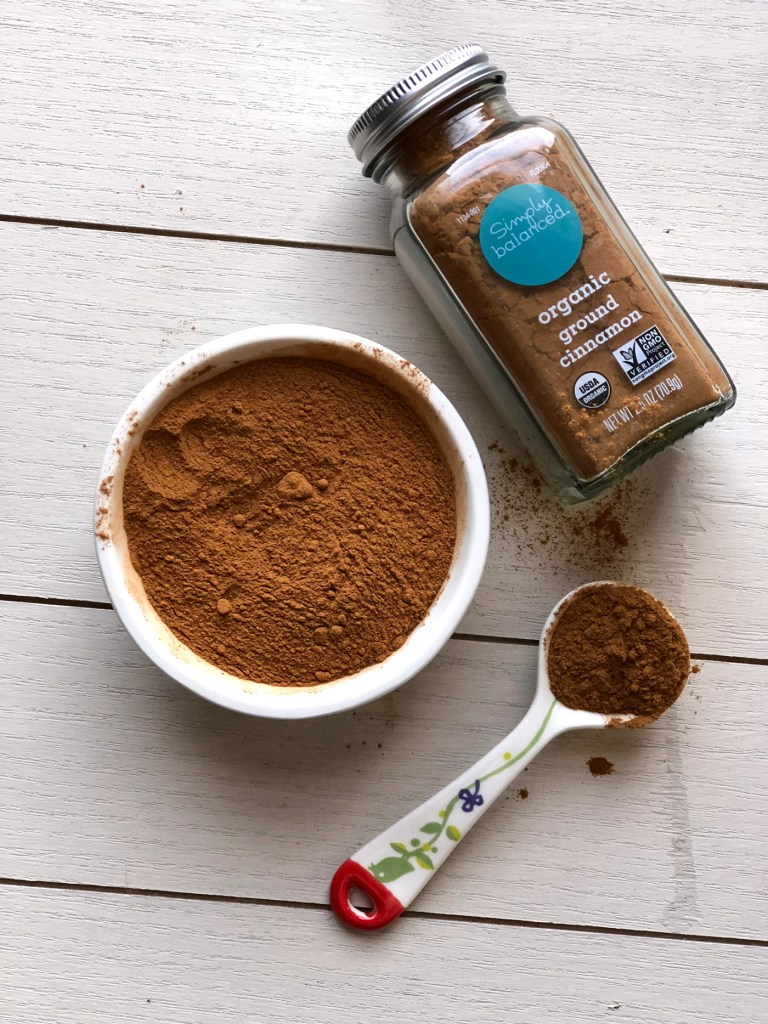Ground cinnamon in a cup, measuring spoon and jar