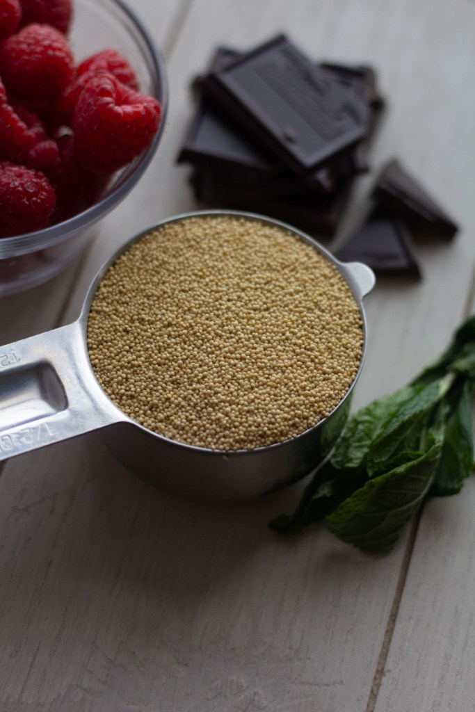 Uncooked amaranth in a measuring cup with dark chocolate squares and raspberries