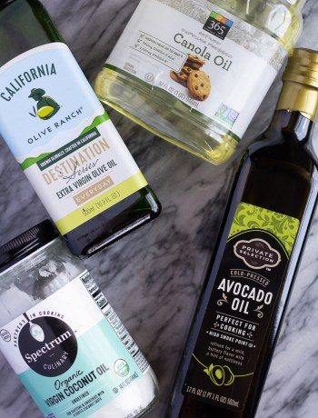 Bottles of extra virgin olive oil, canola oil, avocado oil, and coconut oil