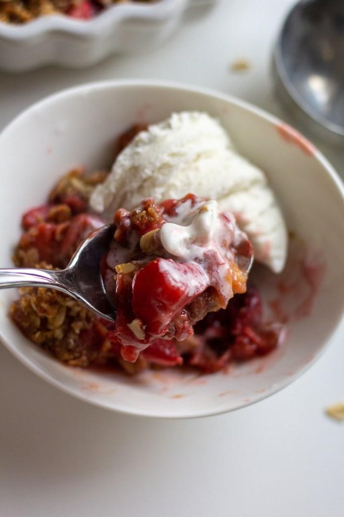 Bite of healthier strawberry rhubarb crisp and vanilla ice cream
