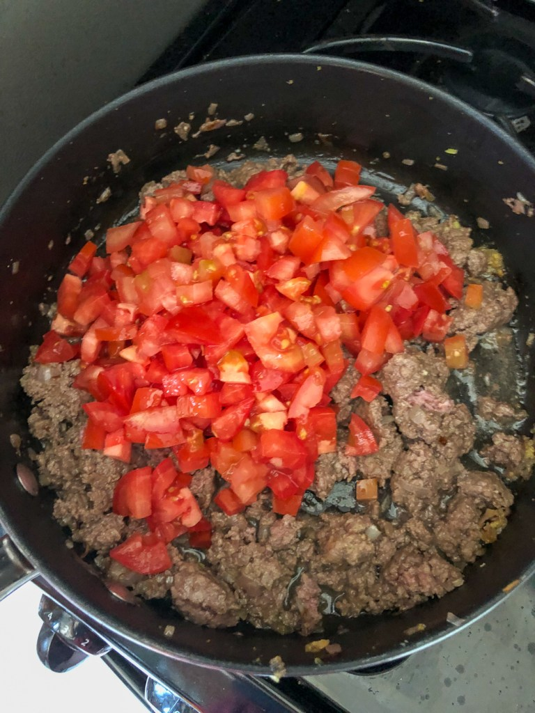 Browned bison in pan with diced tomatoes
