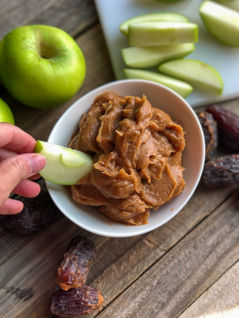 Dipping a Granny smith apple wedge into healthier caramel apple dip