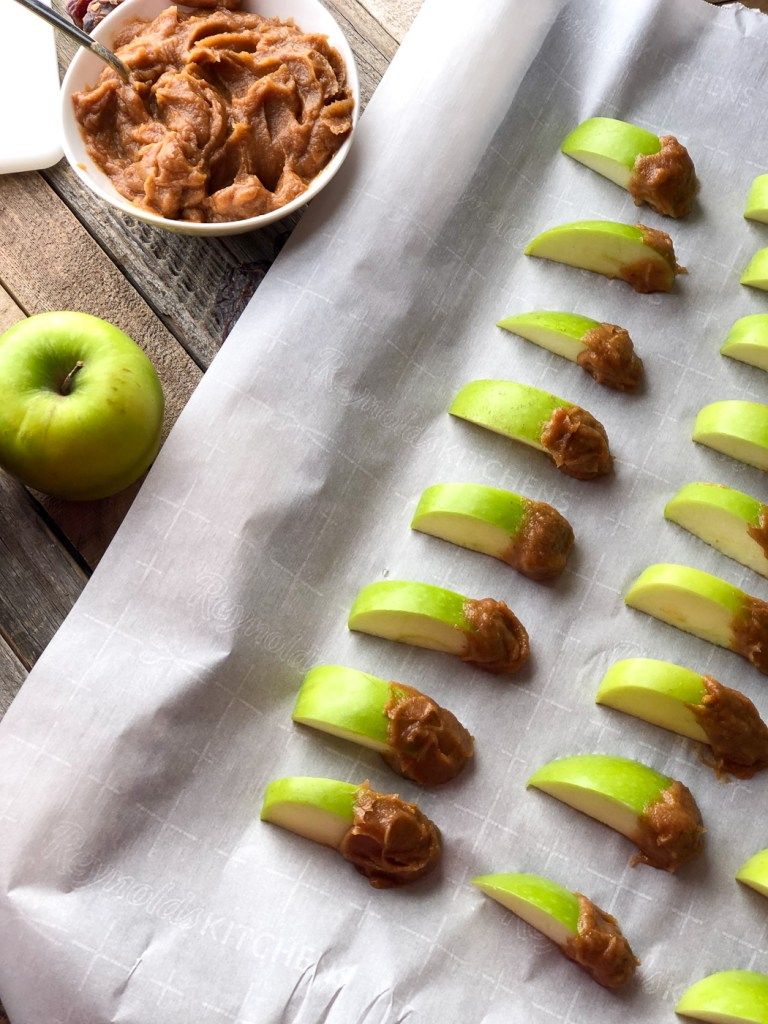 Sliced granny smith apples dipped in healthier date caramel sauce on a baking pan