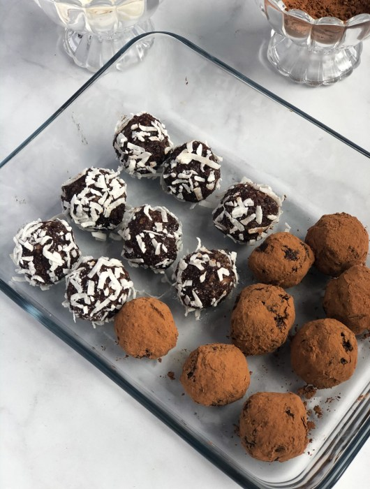 Container of coconut and cocoa covered mint chocolate hemp seed energy bites