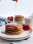 Pouring maple syrup on stack of whole wheat sourdough pancakes
