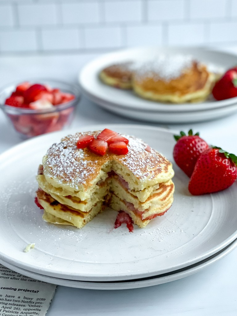 stack of strawberry pancakes with bite taken out
