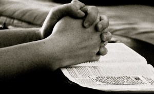 Praying with clasped hands