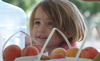 Alexia Wold of Palisade, 5, was selling peaches with her dad, Kevin, and Steve Sherer, also of Palisade, at Saturday's opening of the farmers' market in Meeker.