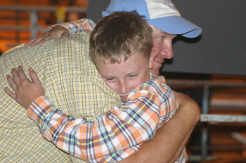 Tristin Pelloni hugs his uncle Todd Morris after winning grand champion market swine in his first year of showing.