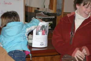 A girl puts money in a donation jar at Meeker Cafe during a benefit dinner Feb. 2 for the Martin family. The event was a sellout. Additional photos on Page 9A.
