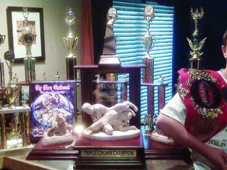 Meeker's T.J. Shelton, a seventh-grader at Barone Middle School is pictured with all the trophies and belt he has won this season. Shelton has won seven national wrestling titles in four different states this season and has compiled a 73-10 record.