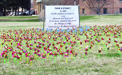 More than 1,100 pinwheels are spinning on the southwest corner of the Rio Blanco County courthouse,  representing abused children in Colorado last year. The sign behind the pinwheels reads: Take a Stand. In 2009 11,339 children in Colorado were abused and neglected, 33 of those children were from Rio Blanco County. Each pinwheel represents 10 abused children. April was first designated Child Abuse Prevention Month in 1983 by President Ronald Reagan. Photo by Bobby Gutierrez