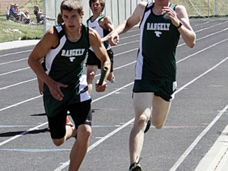 Connor Phelan takes the baton from William Scoggins in the 4x400 relay, which took three seconds off their time.