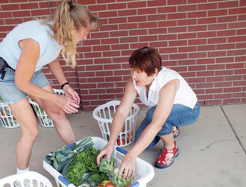 Chris Wills and Melissa Norman chat while transferring fruits and vegetables into Norman's own basket to take home.  The co-op offers approximately $50 of produce for $15. Organic baskets and add-on items are also part of the program.