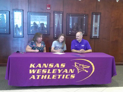Leslie Hernandez signs on to play volleyball for Kansas Wesleyan University while her mother, Beverly, and KWU coach Fred Aubuchon look on. Hernandez is receiving an academic scholarship for $12,600 per year that will cover room and board, plus a $10,000 scholarship toward tuition.