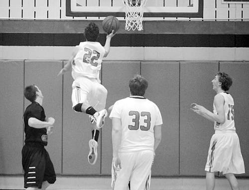 Senior Andrew Morton (22) drives to the basket as junior Layne Mecham (33) and junior Mitchell Webber (15) look on.