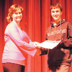 Meeker High School's Amy Chinn presents a check for $10,000 for four years to graduating senior Caleb Lange on behalf of Encana. This was the top money award presented at the MHS 2013-14 Awards Assembly on May 8. It was pointed out that more than 30 percent of the graduating seniors received some kind of award or scholarship this year.