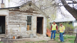 "Jeremy Simmons, right, the director of the Rio Blanco County Department of Environmental Services, and Paul Peronard, left, take a final look at the exterior of the long-unused residence at 1189 Park St. in Meeker. The home was destroyed Friday and Saturday after official found ""substantially radioactive"" uranium ore just inside the front right door and similar ore in the backyard."