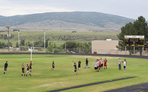 With music blasting from the speakers in Starbuck Stadium, Meeker High School players warm up with a passing drill Monday. Many players have been gathering on their home field on Mondays and Thursdays all summer in preparation of the upcoming season. Practice officially starts Aug. 11 and the annual Cowboys Kickoff Classic golf tournament will be played Aug. 16.