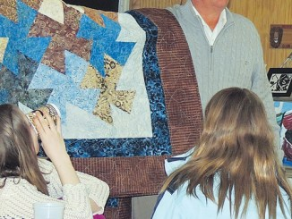 Meeker School Board Member Tom Allen displays a quilt being auctioned Sunday night at the inaugural Meeker Education Foundation dinner in Meeker. Roughly 100 persons took part in the dinner and auction, used to raise funds for Meeker student and staff awards, enrichment opportunities and classroom needs. As of Tuesday, MEF President Mary Strang said the proceeds had not all been totaled.