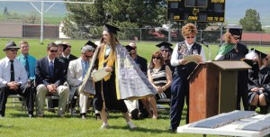 Vicki Crawford, at the podium, just presented MHS Class of 2015 Valedictorian Brittany Smith with a VFW scholarship, one of many scholarships handed out at the commencement on Saturday morning. To the far right is counselor Amy Chinn, who was assisting with the handing out of scholarships.