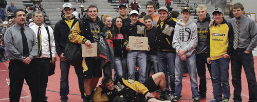 """The Meeker Cowboys won 36 matches in the 2015 Warrior Classic, 24 by pin, which earned bonus points, enough for Meeker to be the """"Best Small School"""" team and fifth overall. Meeker's three-time state champion T.J. Shelton won his first individual Warrior title and was named """"Outstanding Wrestler"""" in the upper weights. Head coach J.C. Watt said he was """"really proud of all the kids"""" and the Warrior Classic was a """"good confidence builder"""" for his team. Pictured are assistant coach Carl Padilla, head coach J.C. Watt, Chase Rule, T.J. Shelton, team managers Abbey Morgan and Avery Watt, Tyler Ilgen, Sheridan Harvey (holding trophy), Jacob Pelloni, Caleb Bradford, Hunter Garcia, Tannen Kennedy, Casey Turner, Garrett Frantz and assistant coach Tyrell Turner. Devon Pontine is in front."""