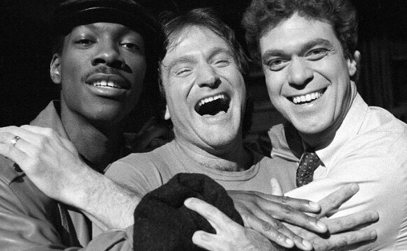 "Robin Williams, center, takes time out from rehearsal at NBC's ""Saturday Night Live"" with cast members Eddie Murphy, left, and Joe Piscopo on February 10, 1984. Williams would appear as guest host on the show."