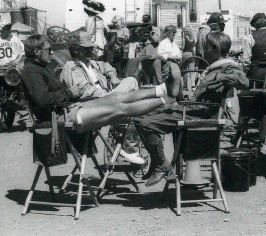 River Phoenix chilling with Steven Spielberg and Harrison Ford on the set of