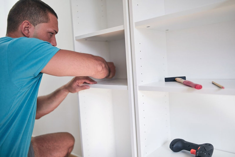 A-carpenter-working-to-Attach-Closet-Shelves-to-Wall