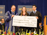 ALEXANDER BROWN/THE HOYA Senior Class Fund Co-Chairs Elizabeth Abello (COL '14) and Peter Brigham (SFS '14) present $155,640.40 to University President DeGioia.