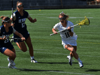 MARGARET FOUBERG/ THE HOYA | Junior attack Natalia Lynch cradles by two UC Davis Defenders on March 24. Lynch tallied 2 goals and 2 assists in the win.