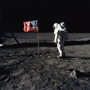 """Astronaut Buzz Aldrin, lunar module pilot of the first lunar landing mission, poses for a photograph beside the deployed United States flag during an Apollo 11 Extravehicular Activity (EVA) on the lunar surface. The Lunar Module (LM) is on the left, and the footprints of the astronauts are clearly visible in the soil of the Moon. Astronaut Neil A. Armstrong, commander, took this picture with a 70mm Hasselblad lunar surface camera. While astronauts Armstrong and Aldrin descended in the LM, the """"Eagle"""", to explore the Sea of Tranquility region of the Moon, astronaut Michael Collins, command module pilot, remained with the Command and Service Modules (CSM) """"Columbia"""" in lunar-orbit.; Image credit"""