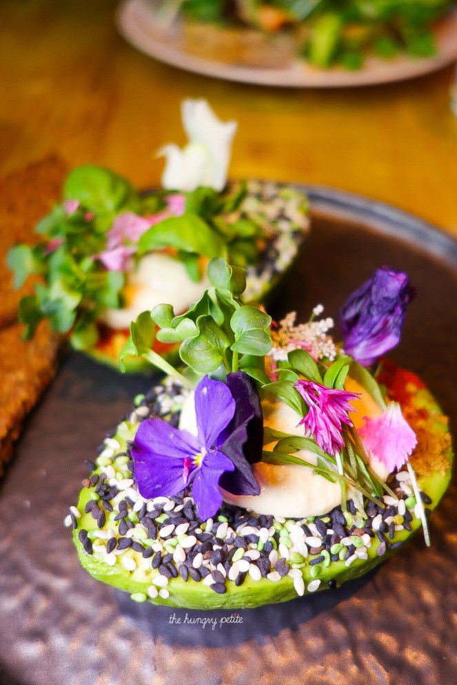 The Avo Garden - Two avocado halves filled with hummus, decorated with spices & flowers and sidekicked by crispy multigrain toast.