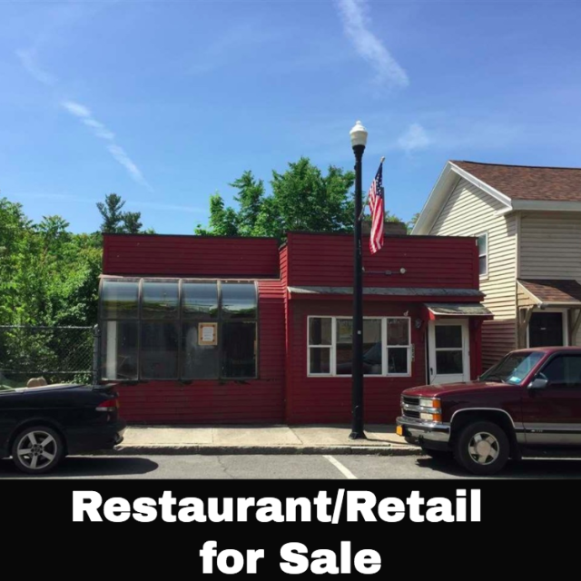 Restaurant or retail location featuring walk-in cooler with glass front street display. kitchen equipment includes 2 reach-ins, commercial hood, range, steam table, 2 sinks, commercial oven, propane hook-ups, dessert cooler and freezer.