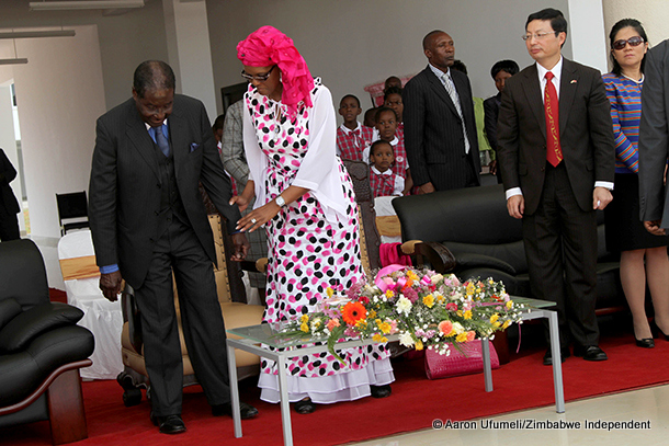 President Robert Mugabe gets a helping hand from his wife First Lady Grace Mugabe at the official opening of Amai Mugabe Junior School in Mazowe.