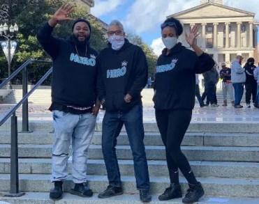 Leah Alexander-Otukpe, Sekou Writes and Albry Lockhart hold up HERO Hoodies