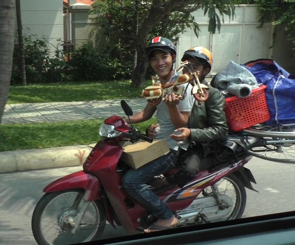 Selling wooden motorcycle while driving another motorcycle