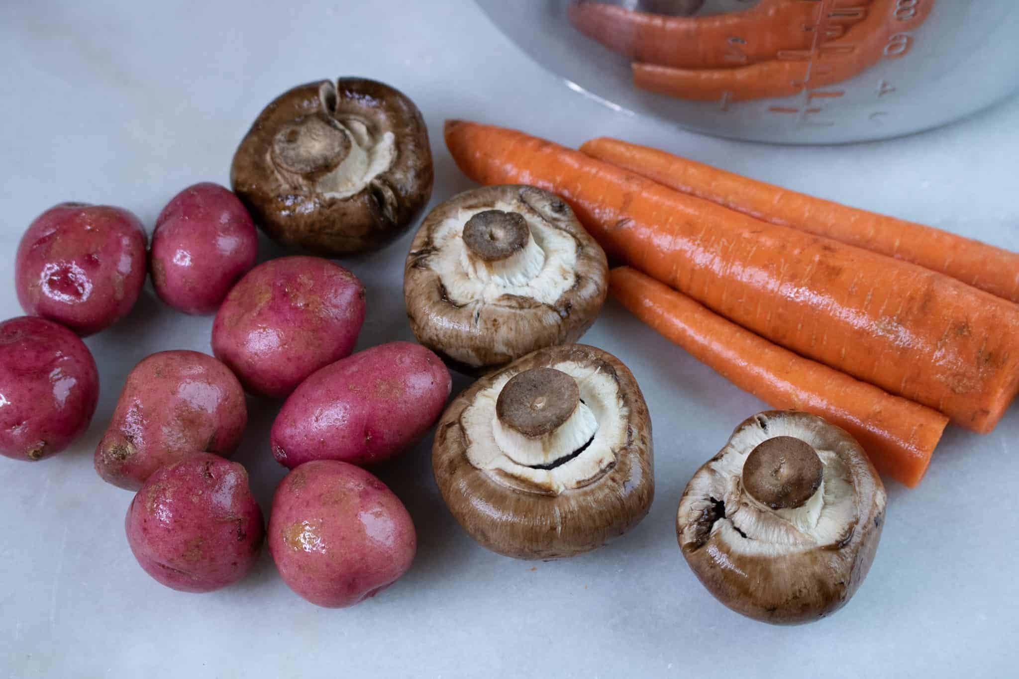 This easy instant pot pot roast recipe includes potoatoes, mushrooms, and carrots.